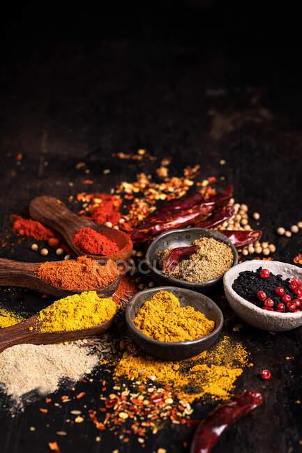 Assortiment d'épices aromatiques colorées dans des bols et des cuillères en bois disposées sur une table noire avec des condiments dispersés — Photo de stock