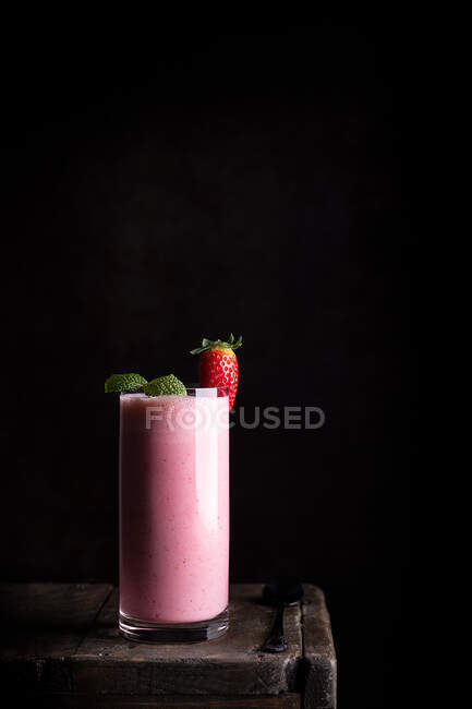 Delicious healthy homemade milkshake with fresh strawberry garnished with green mint leaves served in glass on wooden table against black background — Stock Photo