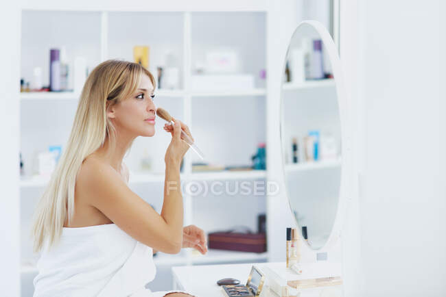 Side view female with perfect skin applying powder on face while doing makeup at home and looking in mirror — Stock Photo