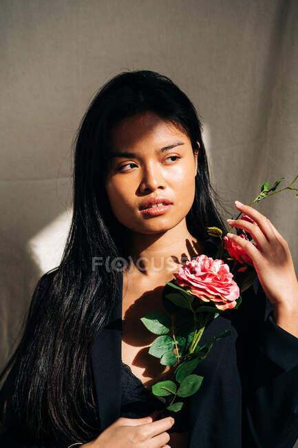 Молодая очаровательная этническая модель в черном халате, прикасаясь к волосам, отводя взгляд, держа розовый букет роз в тени от солнечного света — стоковое фото
