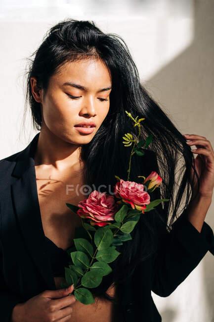 Молодая очаровательная модель этнической женщины в черном халате, прикасаясь к волосам, глядя на букет розовых роз в тени от солнечного света — стоковое фото
