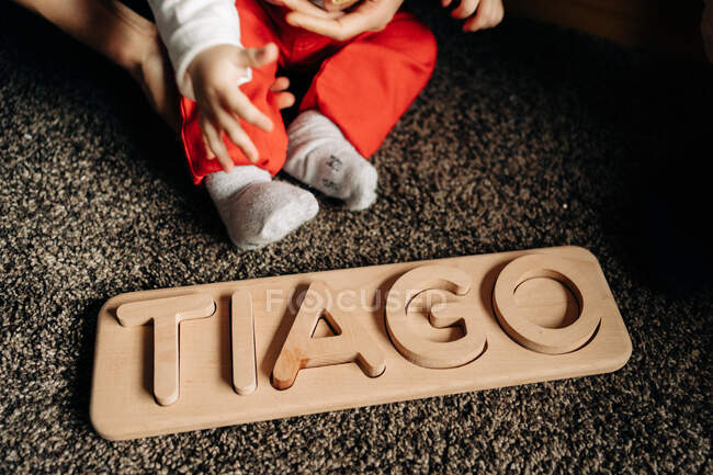 Cropped unrecognizable little baby playing on floor with wooden toy with Tiago name letters — Fotografia de Stock