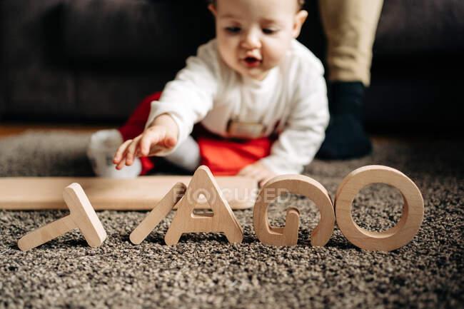 Adorable bebé jugando en el suelo con juguete de madera con letras de nombre Tiago - foto de stock
