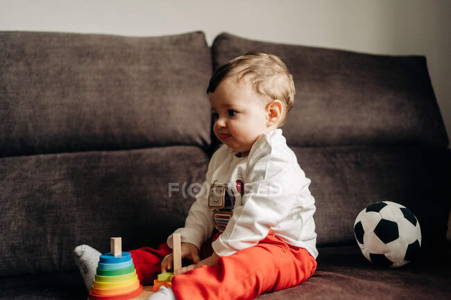 Side view adorable little boy sitting on sofa and playing with colorful wooden cone at home — Stock Photo