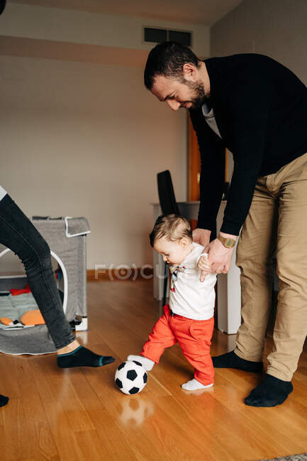 Funny little boy kicking ball while playing with young father and crop unrecognizable mother at home — Stock Photo