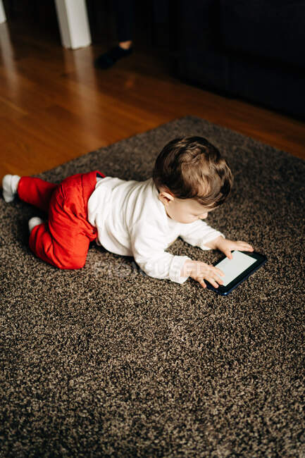 From above content little baby boy lying on fluffy carpet and watching funny video on mobile phone in light living room — Stock Photo