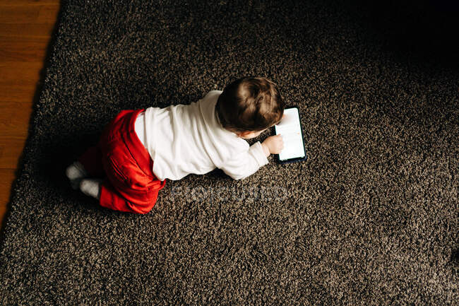 From above content little baby boy lying on fluffy carpet and watching funny video on mobile phone in light living room — Fotografia de Stock