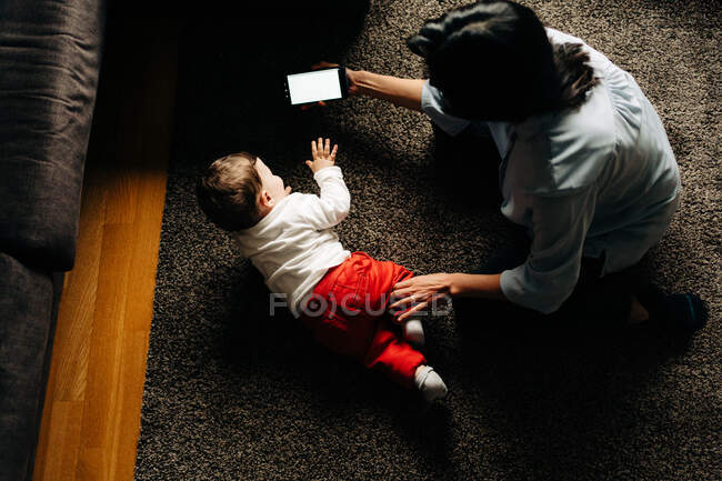From above anonymous mother in casual wear showing cartoon on mobile phone to adorable little son while sitting together on carpet in living room — Fotografia de Stock