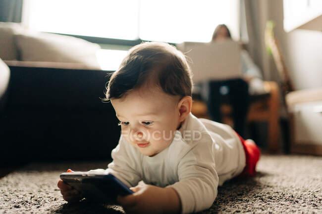 Contenuto bambino piccolo sdraiato su un tappeto soffice e guardando video divertenti sul telefono cellulare in salotto leggero — Foto stock