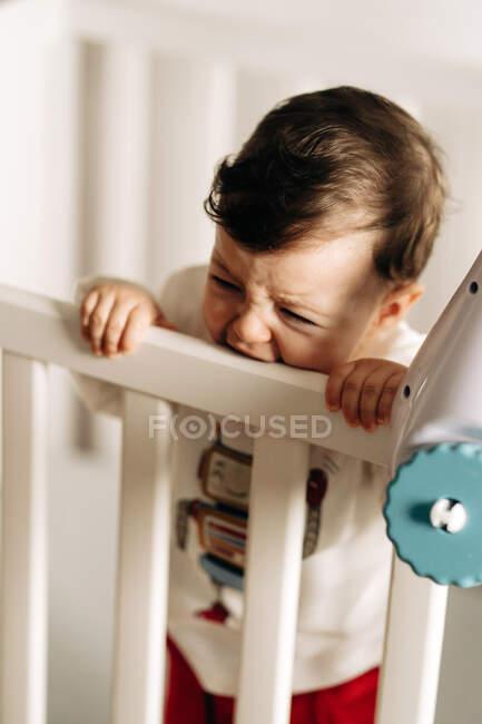 Adorable niño frunciendo el ceño en ropa casual de pie en cuna y morder riel de madera - foto de stock