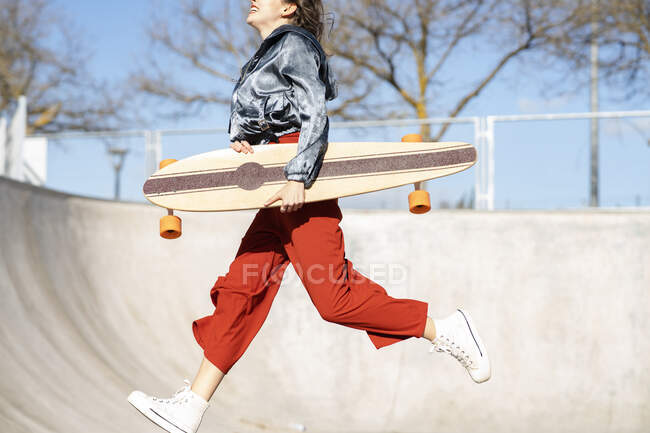 Side view of cropped unrecognizable happy young female in stylish apparel jumping on concrete skate park — Stock Photo