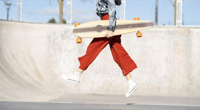 From below side view of cropped unrecognizable happy young female in stylish apparel jumping on concrete skate park — Stock Photo