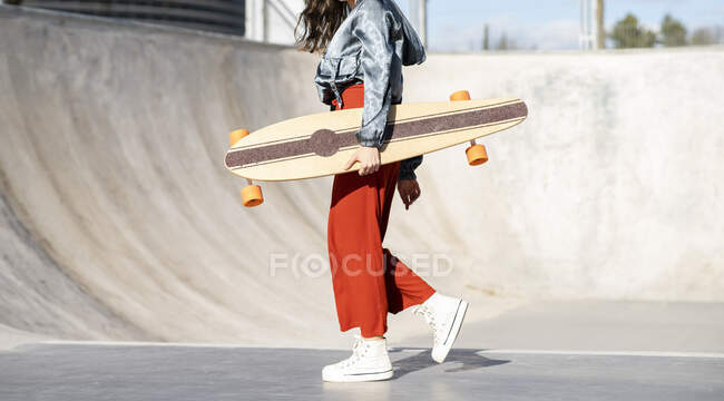 Side view of cropped unrecognizable happy young female in stylish apparel walking with longboard on concrete skate park — Stock Photo