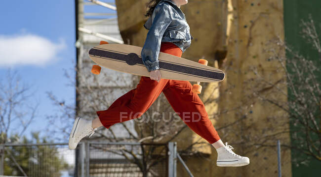 From below side view of cropped unrecognizable happy young female in stylish apparel jumping on the street — Stock Photo