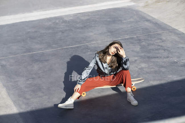 From above of young woman in stylish clothes touching forehead while sitting on longboard and looking at camera — Stock Photo
