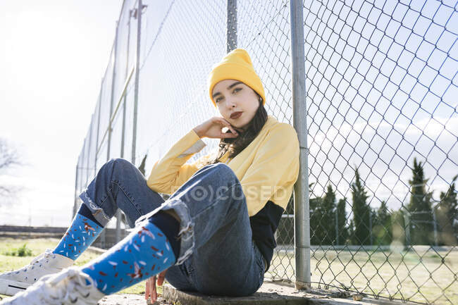 Female teenager in trendy apparel with red lips looking at camera while leaning on grid fence in town in sunlight — Stock Photo