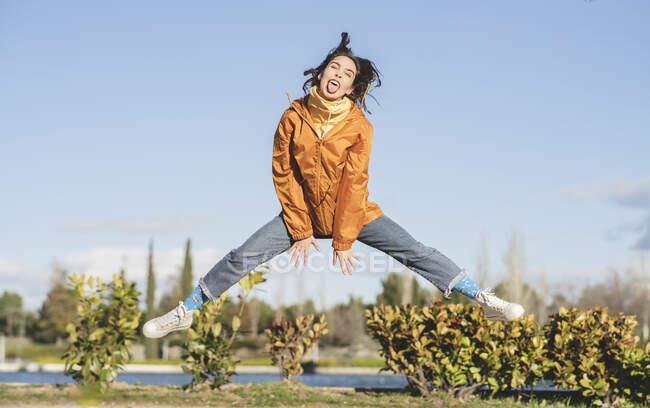 Активная самка прыгает с высунутым языком и раздвигает ноги о кусты и пруд под голубым облачным небом — стоковое фото