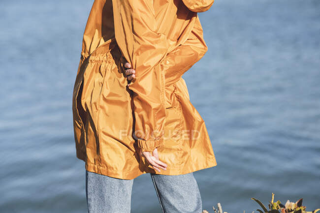 Back view of cropped unrecognizable female teenager in casual wear with hands behind back standing against rippled river — Stock Photo