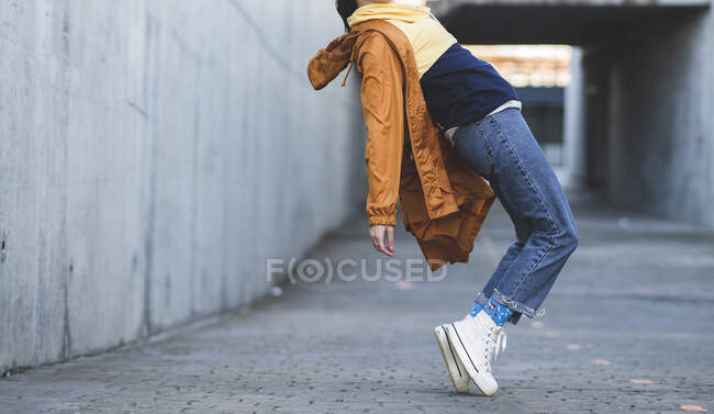 Side view of cropped unrecognizable female teenager in casual clothes having fun on city road while looking forward — Stock Photo