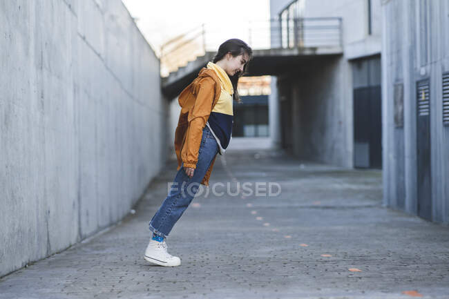 Side view of content female teenager in casual clothes having fun leaning forward on city road while looking down — Stock Photo