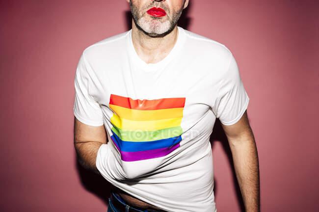 Cosecha anónima joven homosexual masculino con lápiz labial rojo y camiseta con bandera de arco iris sobre fondo rosa - foto de stock