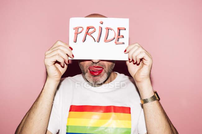 Бунтівний бородатий гомосексуаліст з червоними губами і манікюр робить сірники язиком, показуючи і прикриваючи обличчя папером з текстом гордості на рожевому фоні. — стокове фото