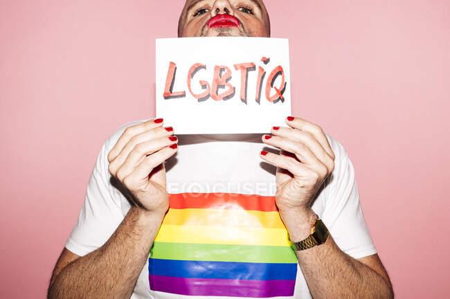 Бунтівний бородатий гомосексуаліст з червоними губами і манікюр робить сірники, показуючи і покриваючи обличчя папером ЛГБТІК текст на рожевому фоні — стокове фото