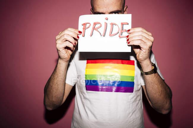 Мятежный бородатый гомосексуалист с красными губами и маникюром гримасничает, показывая и покрывая лицо бумагой с надписью Гордость на розовом фоне — стоковое фото