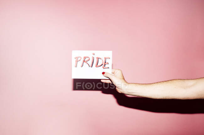 Crop unrecognizable homosexual person with manicure demonstrating white paper with PRIDE inscription against pink background — Photo de stock
