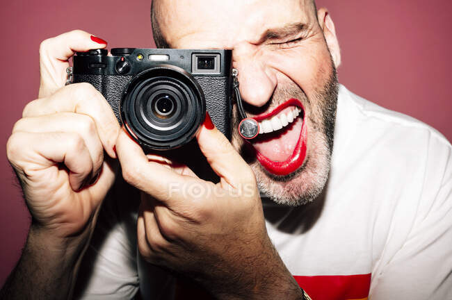 Crop bearded expressive homosexual male photographer in red lips and manicure taking picture on vintage camera against pink background — Stock Photo