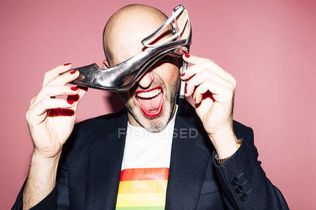 Eccentric bald bearded homosexual male with red lips and manicure in shirt with LGBT flag yelling and covering eyes with high heeled shoe against pink background — Stock Photo