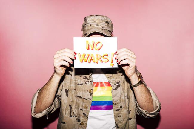 Невпізнаваний бородатий ексцентричний чоловік середнього віку в сорочці з ЛГБТ-прапором з манікюром з папером з написом