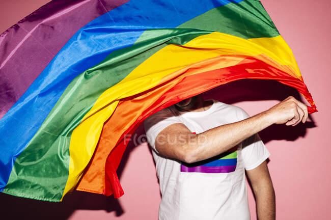 Hombre homosexual irreconocible con camiseta blanca ondeando bandera LGBT contra fondo rosa - foto de stock