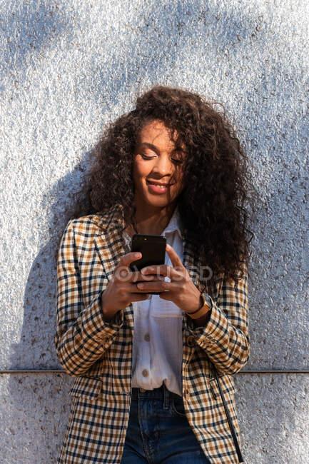 Афроамериканка в модному одязі з кучерявим волоссям, стоячи на вулиці біля бетонної стіни. — стокове фото
