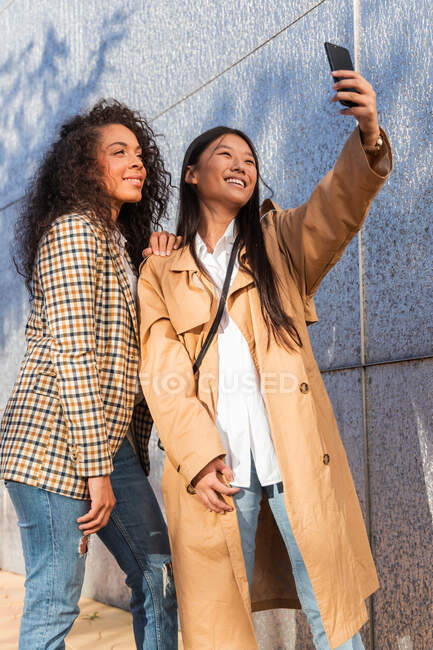 Optimistic ethnic female friends in trendy outfits standing on city street and taking selfie while having break — Stock Photo