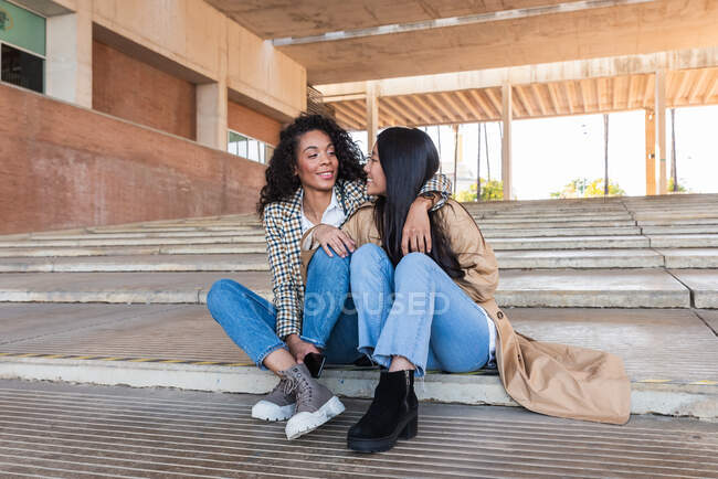 Happy African American woman with toothy smile and positive Asian female looking at each other while sitting on concrete stairs — Stock Photo