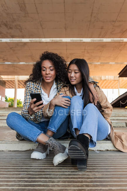 Optimistic ethnic female friends in trendy outfits sitting on city street and chatting on mobile phone — Stock Photo