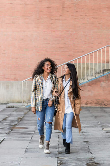 Delighted female friends with toothy smiles wearing trendy clothes looking away while walking together in town — Stock Photo