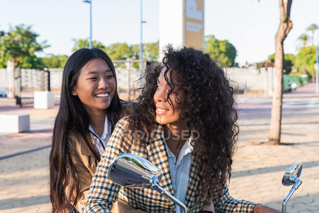 Mujer asiática optimista con sonrisa dentada y mujer afroamericana satisfecha con el pelo rizado mirándose mientras está sentada en la moto — Stock Photo