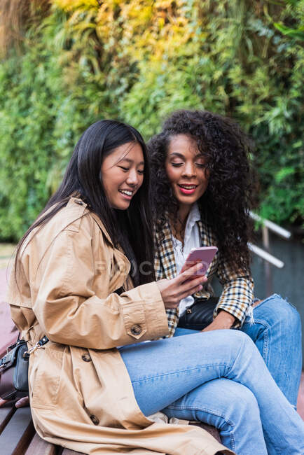 Pleasant Asian female with toothy smile showing video on smartphone to happy black woman while spending time together — Stock Photo