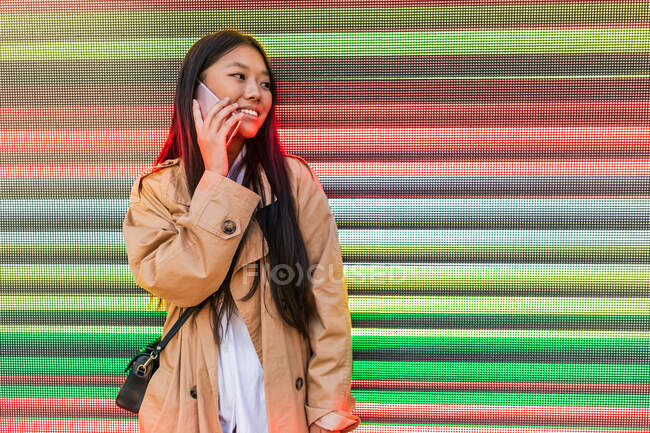 Optimistic Asian female in trendy outfit with toothy smile looking away and having conversation on mobile phone against digital wall — Photo de stock