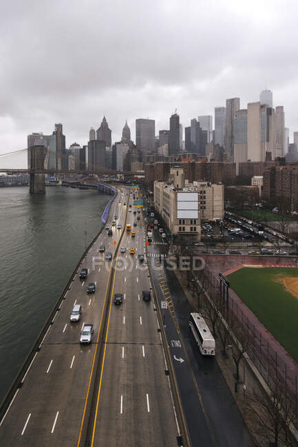 Manhattan district with urban skyscrapers and suspension bridge over rippling East River under gloomy cloudy sky — Stock Photo