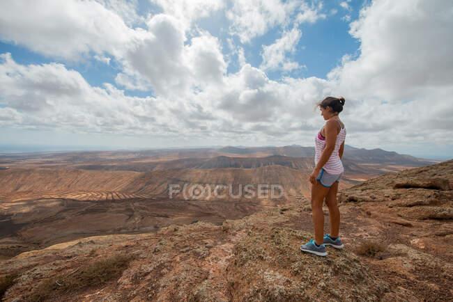 Самка - туристка у повсякденному одязі стоїть на скелястому пагорбі і в ясний день насолоджується просторою горбистою долиною. — стокове фото