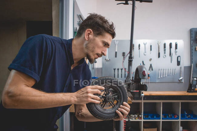 Side view of serious adult male mechanic assembling wheel of electric scooter while working in professional workshop — Stock Photo