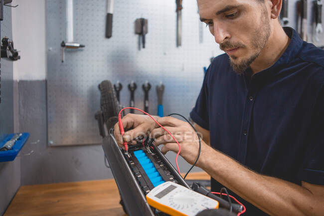 Side view of concentrated skilled male mechanic using multimeter while testing battery of electric scooter in workshop — Stock Photo