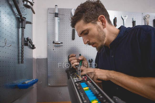 Vista lateral del mecánico masculino experto concentrado usando multímetro mientras prueba la batería de scooter eléctrico en el taller - foto de stock