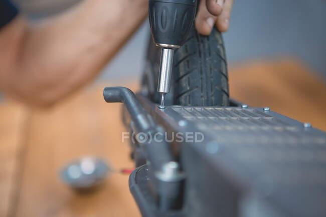 Vista lateral de la cosecha mecánica masculina anónima con destornillador rueda de fijación de scooter eléctrico en taller - foto de stock