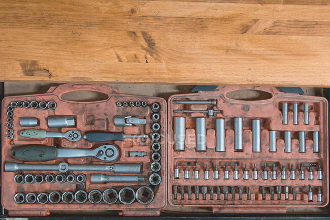 From above of old box with screwdriver and various nozzles and wrenches for auto maintenance and repair service on wooden table — Stock Photo
