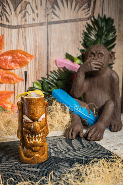 Brown sculptural tiki mug with alcohol drink decorated with straw and ice placed amidst dry grass against green plant with feather on blurred background — Stock Photo