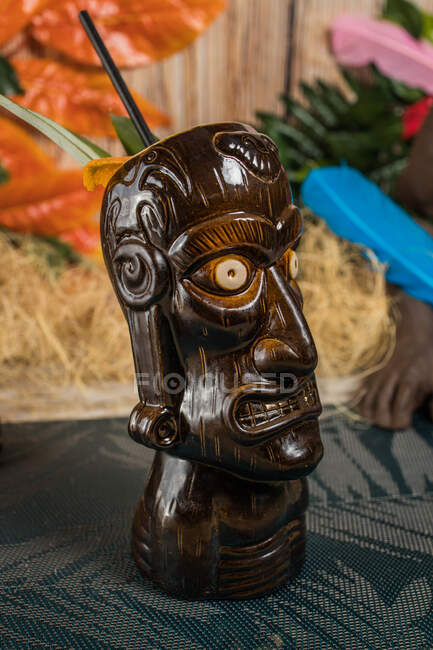 Brown sculptural tiki mug with alcohol drink decorated with straw and ice placed on table — Stock Photo